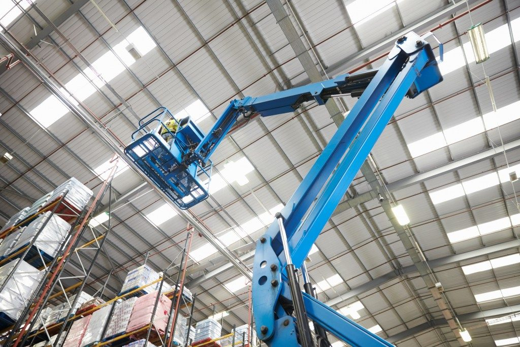 Moving stock in a warehouse uppar shelves with a cherry picker