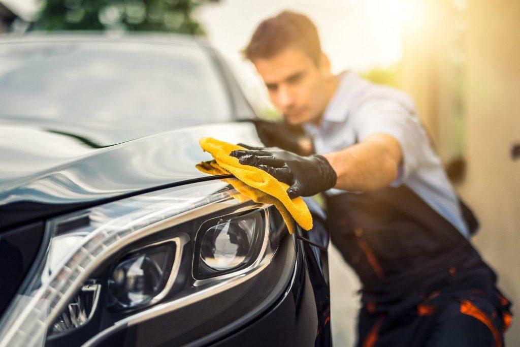 man wiping a car
