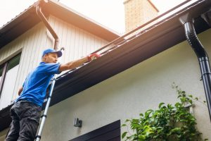 Man cleaning rain gutter