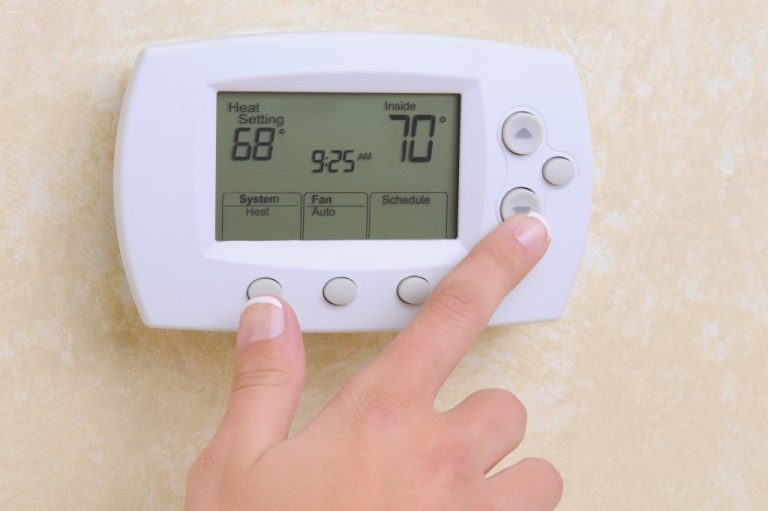 Woman setting the room temperature