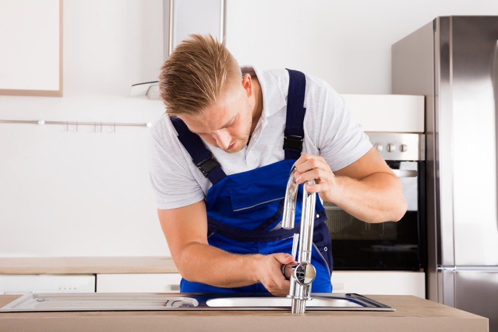 Plumber fixing faucet in a kitchen