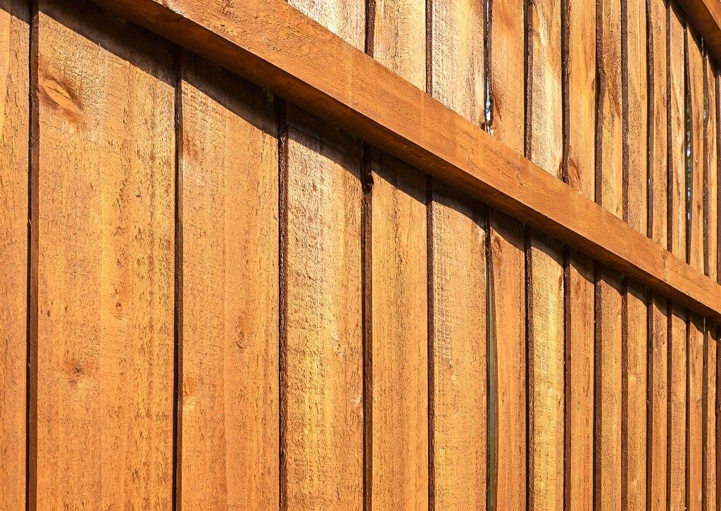 A section of brown, vertical, overlapped wooden garden fence