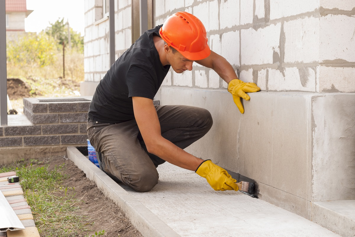 Worker plastering the home foundation