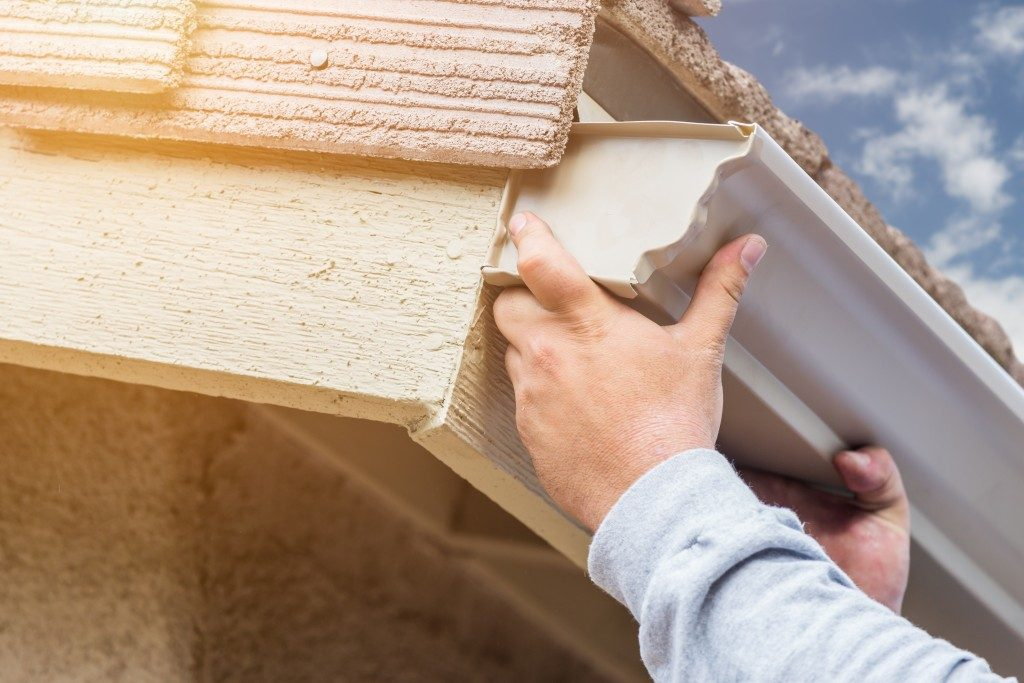 Man putting seamless gutter to house