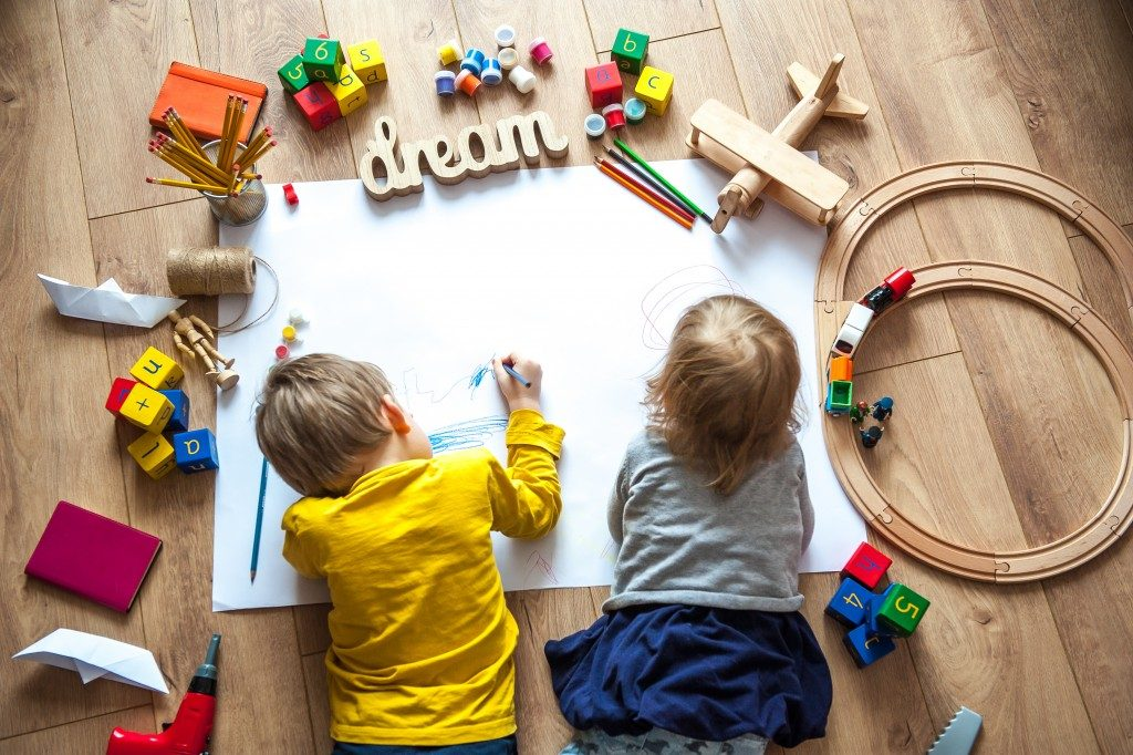 Children drawing beside wooden toys