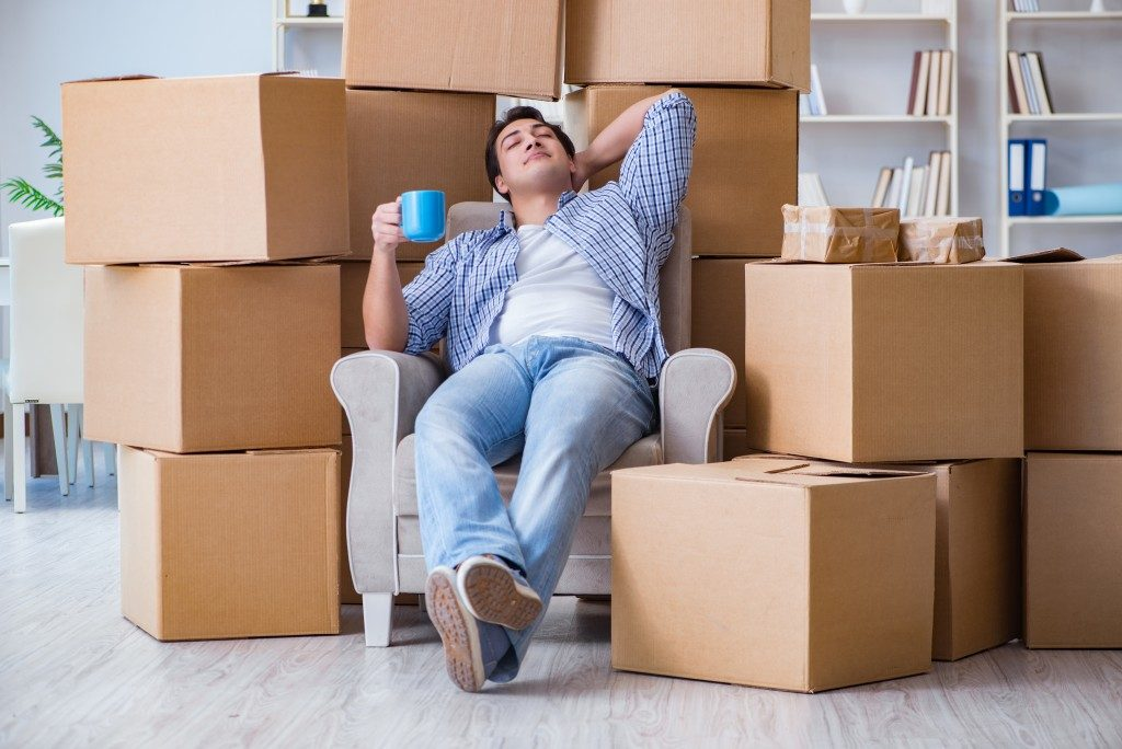 Man sitting beside boxes