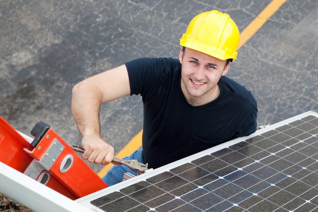 Electrician in hard hat installing solar panels