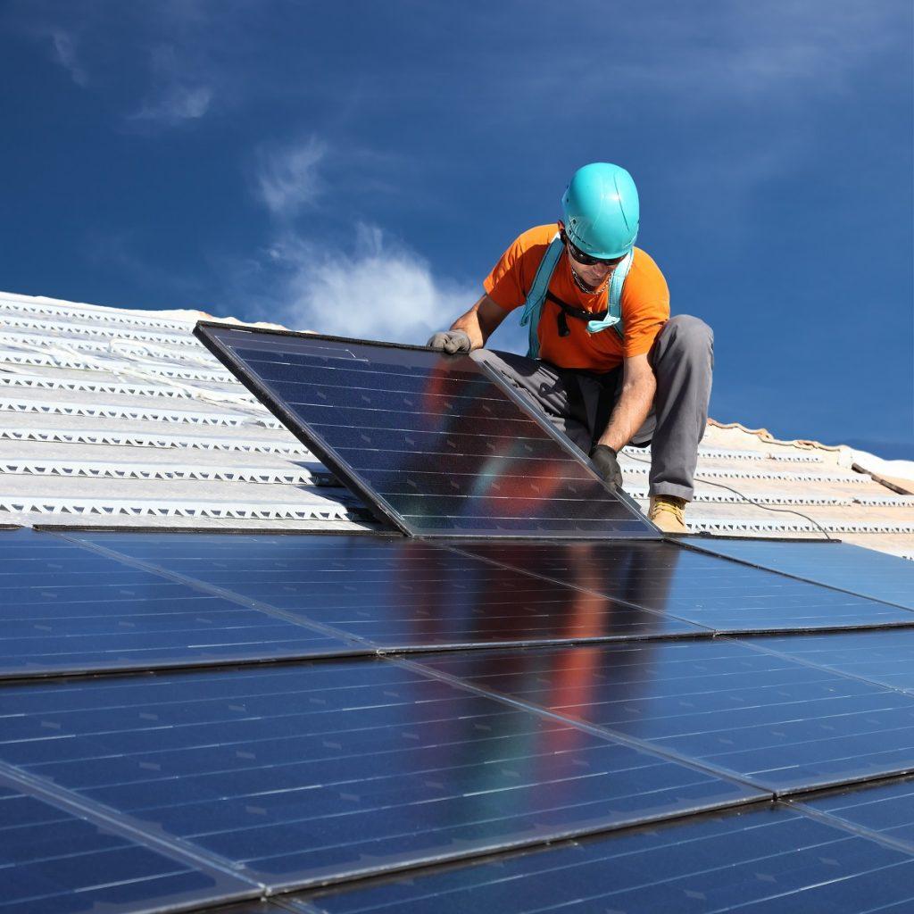 Worker installing solar panels
