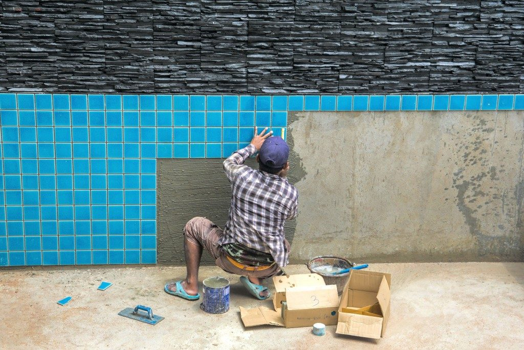 Man installing swimming pool tiles