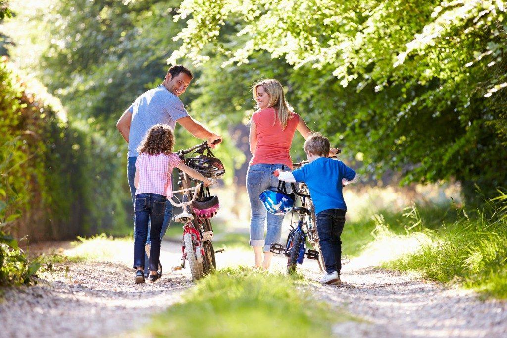 Family pushing bikes
