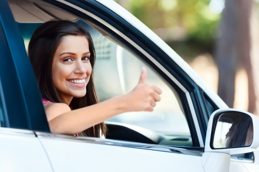 Woman riding a car while doing a thumbs up