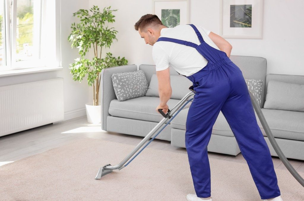 Man cleaning the carpet using a vacuum