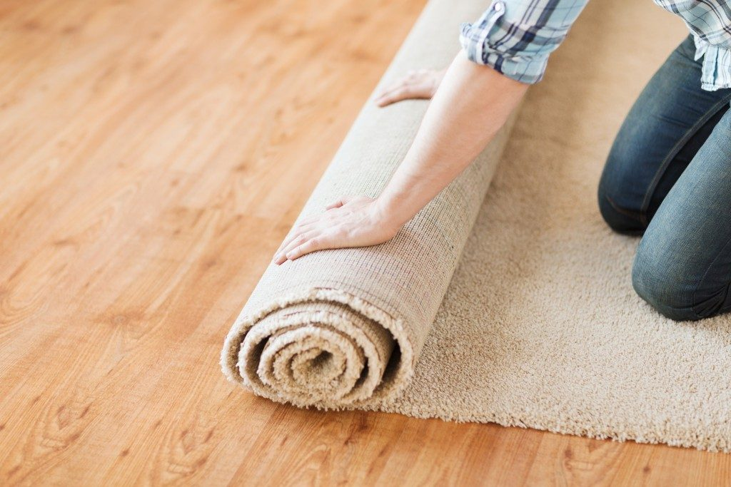man unrolling a carpet
