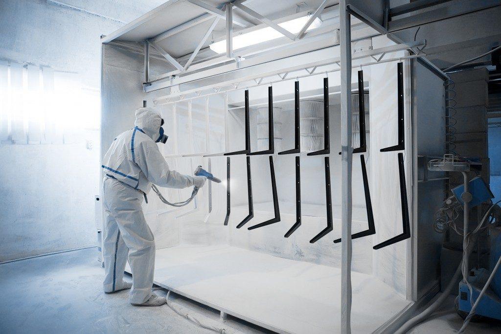 Worker powder coating metal frames