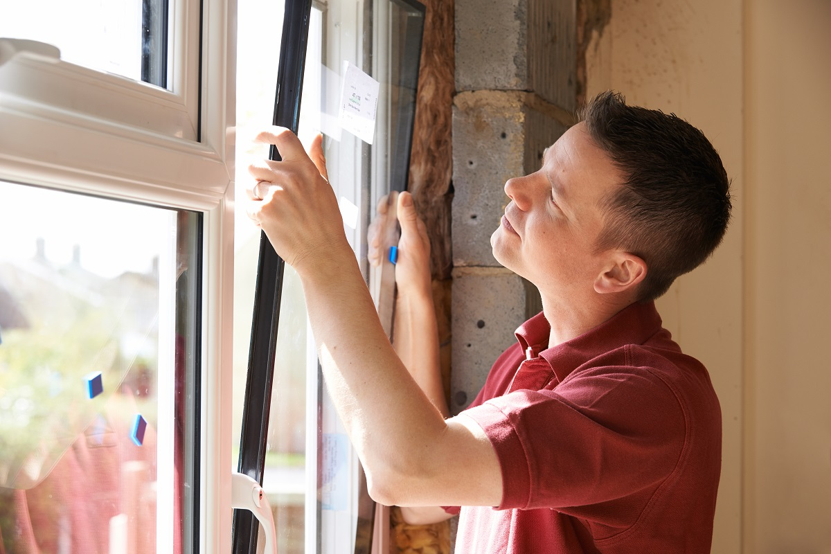 man installing window