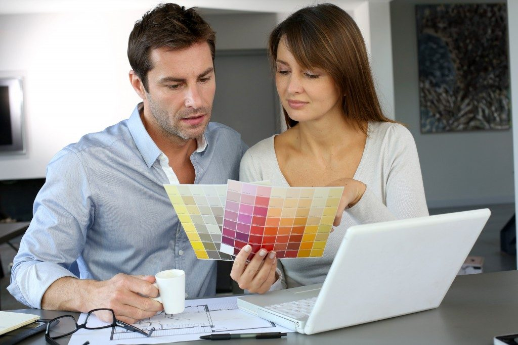 Couple choosing between colors for house