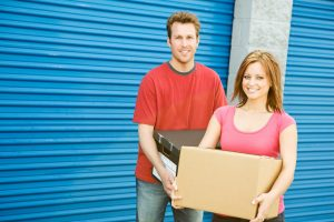 Couple carrying boxes to storage unit