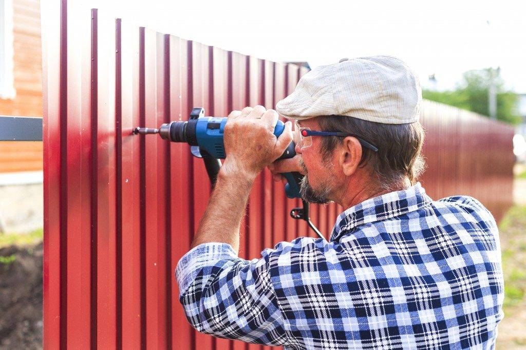 man installing a metal fence