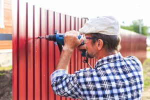 man installing a metal fence