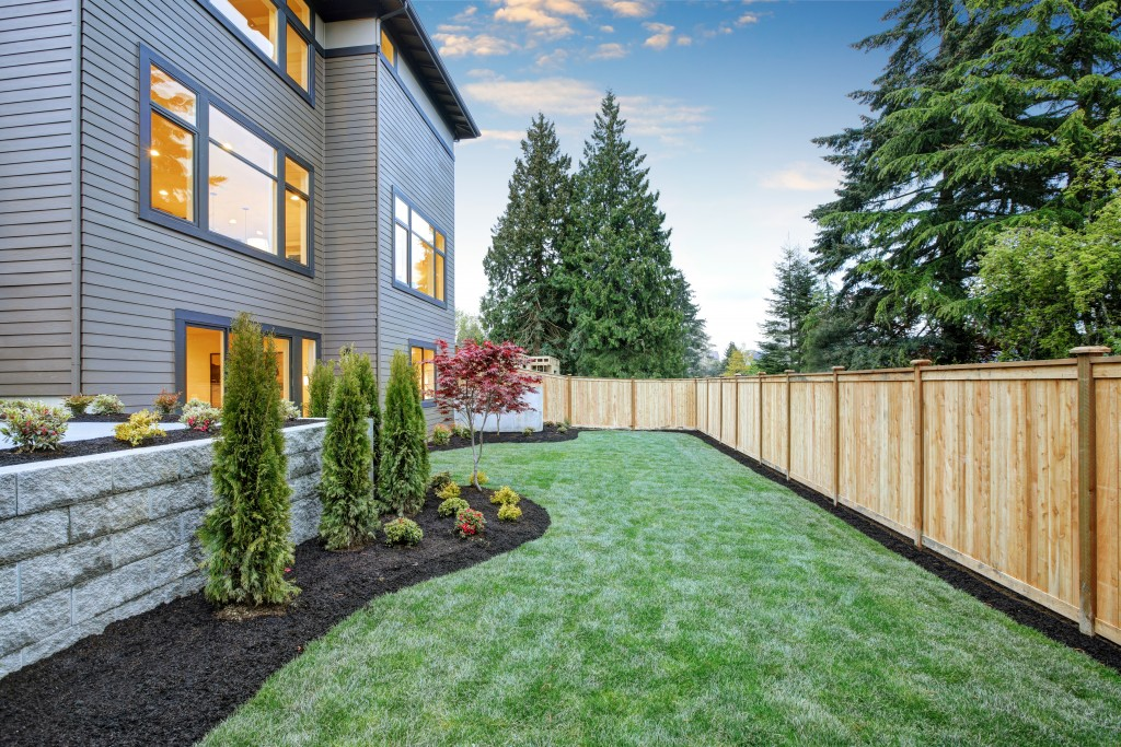 Nice backyard landscape with well kept lawn, flower beds and wooden fence.