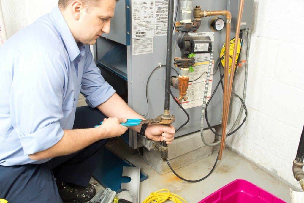 plumber fixing an office's water sewage machine