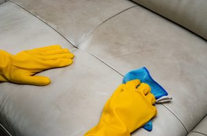yellow gloves cleaning furniture