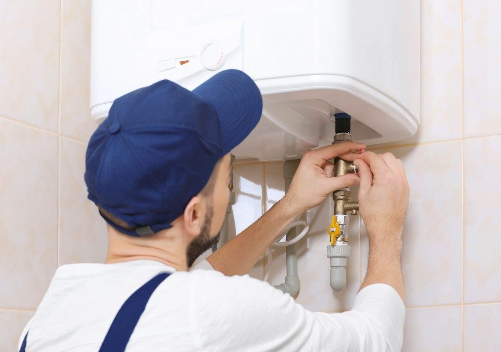 man tigthening the connection tube of the plumbing system in the bathroom