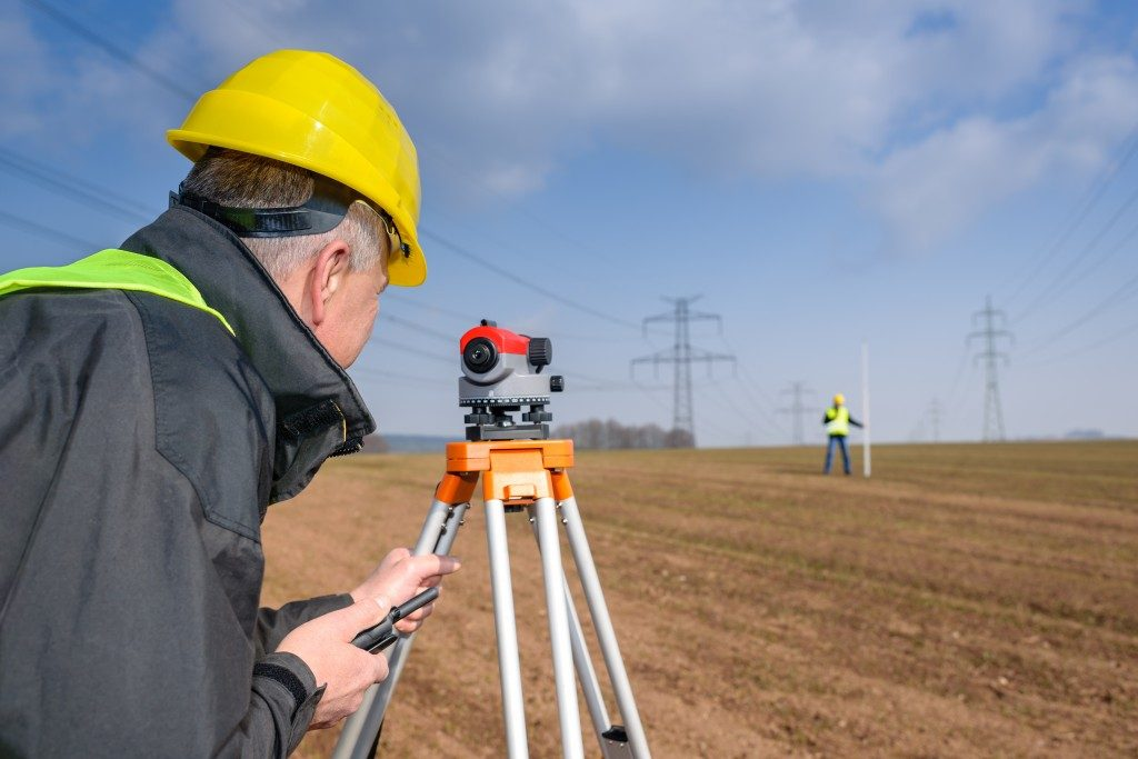 Land surveyors measuring with tacheometer