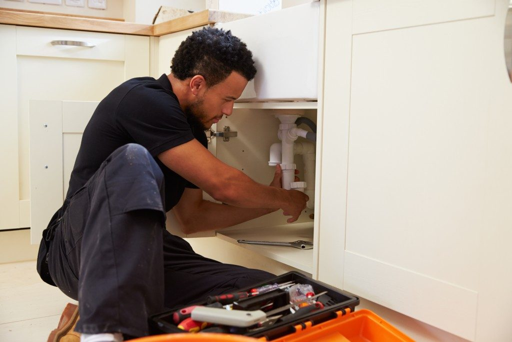 man fixing the plumbing of the kitchen's sink