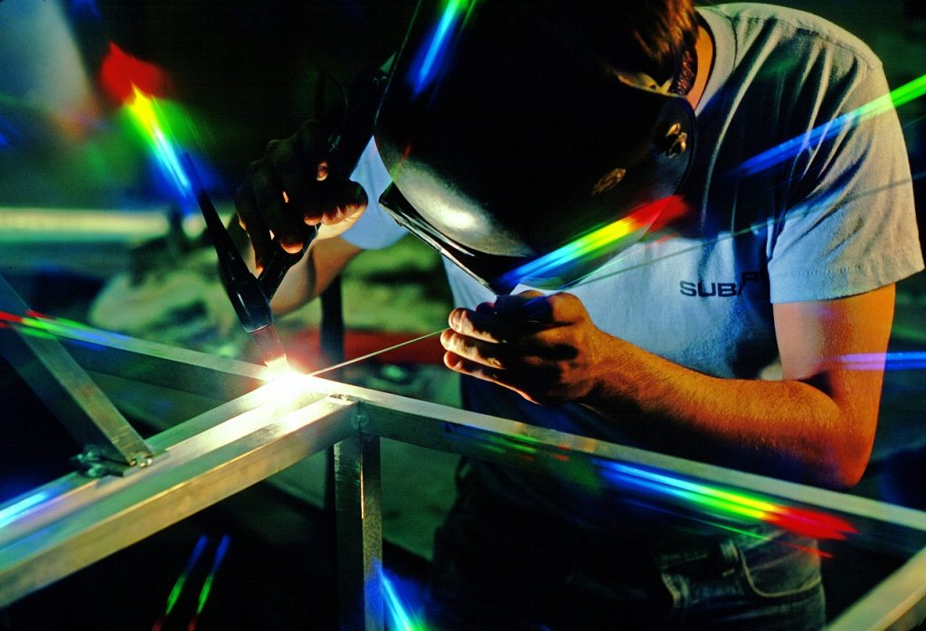 Man welding with colorful lights