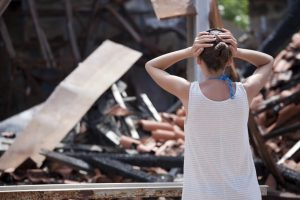 woman looking at her burnt home