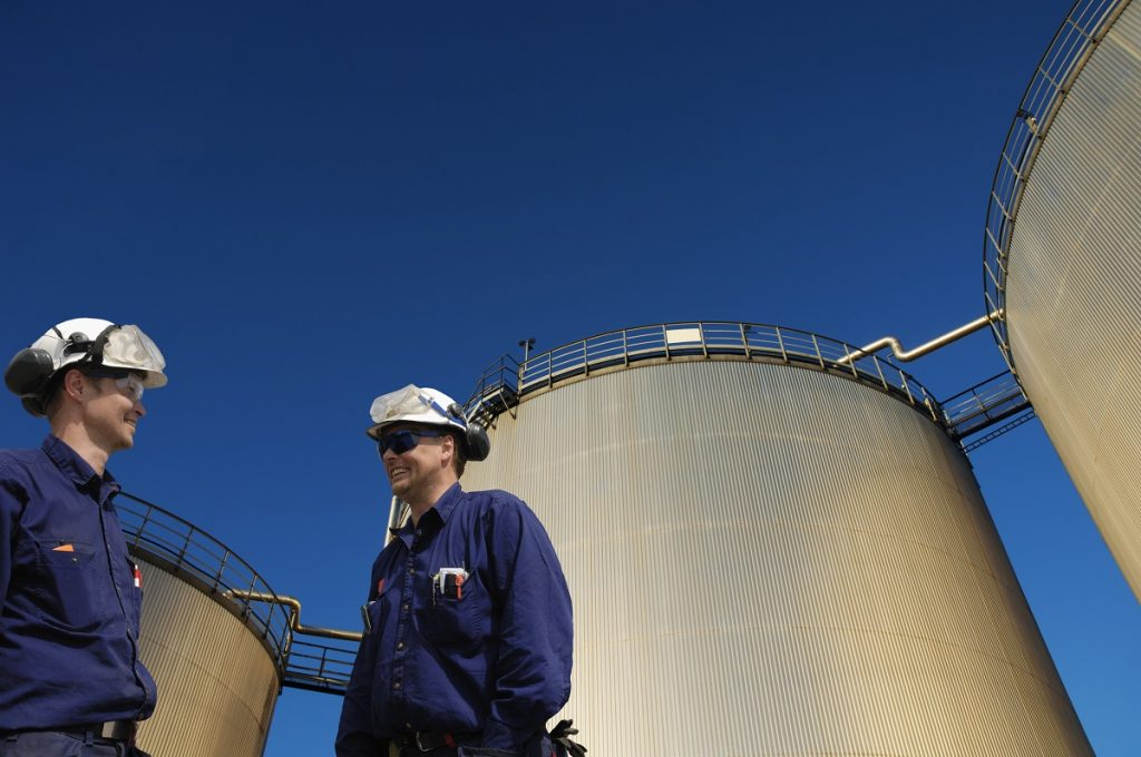 oil and gas workers in front of large fuel storage tanks