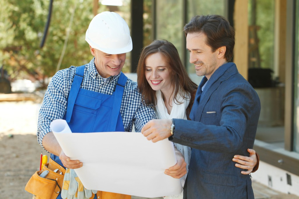 contactor showing and discussing house blueprint to couple