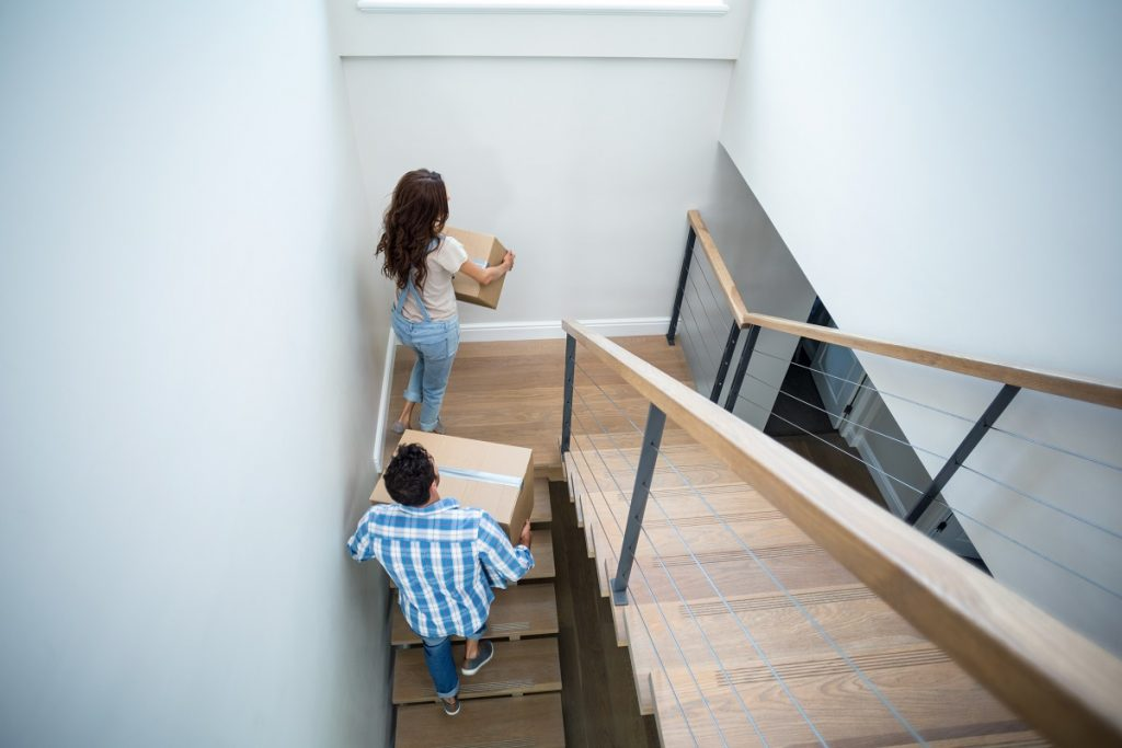 Couple carrying boxes upstairs