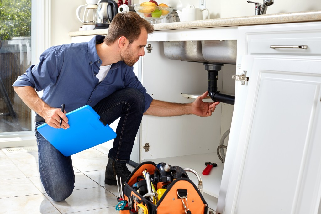 man checking sink plumbing