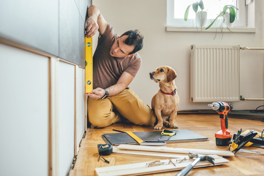 Man doing DIY work with his dog